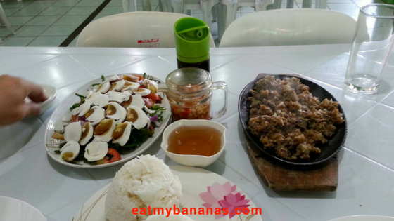 Paco salad, sisig, rice, and condiments placed on a white table.
