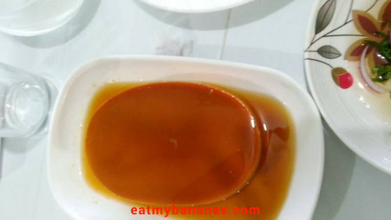One whole leche flan on a white dish.