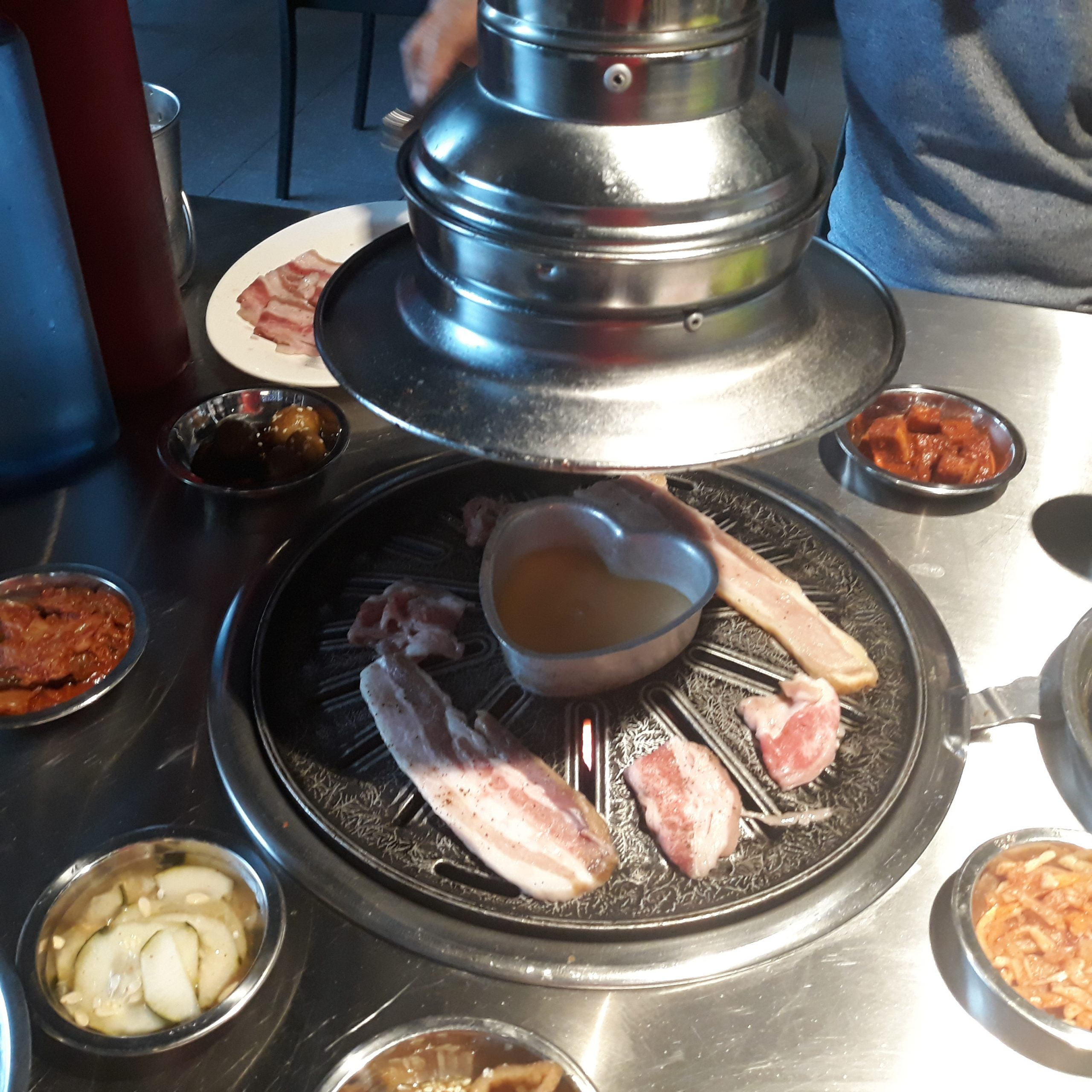 Grilling some Seoulgyupsal meat with their special cheese sauce in the middle of the griller.