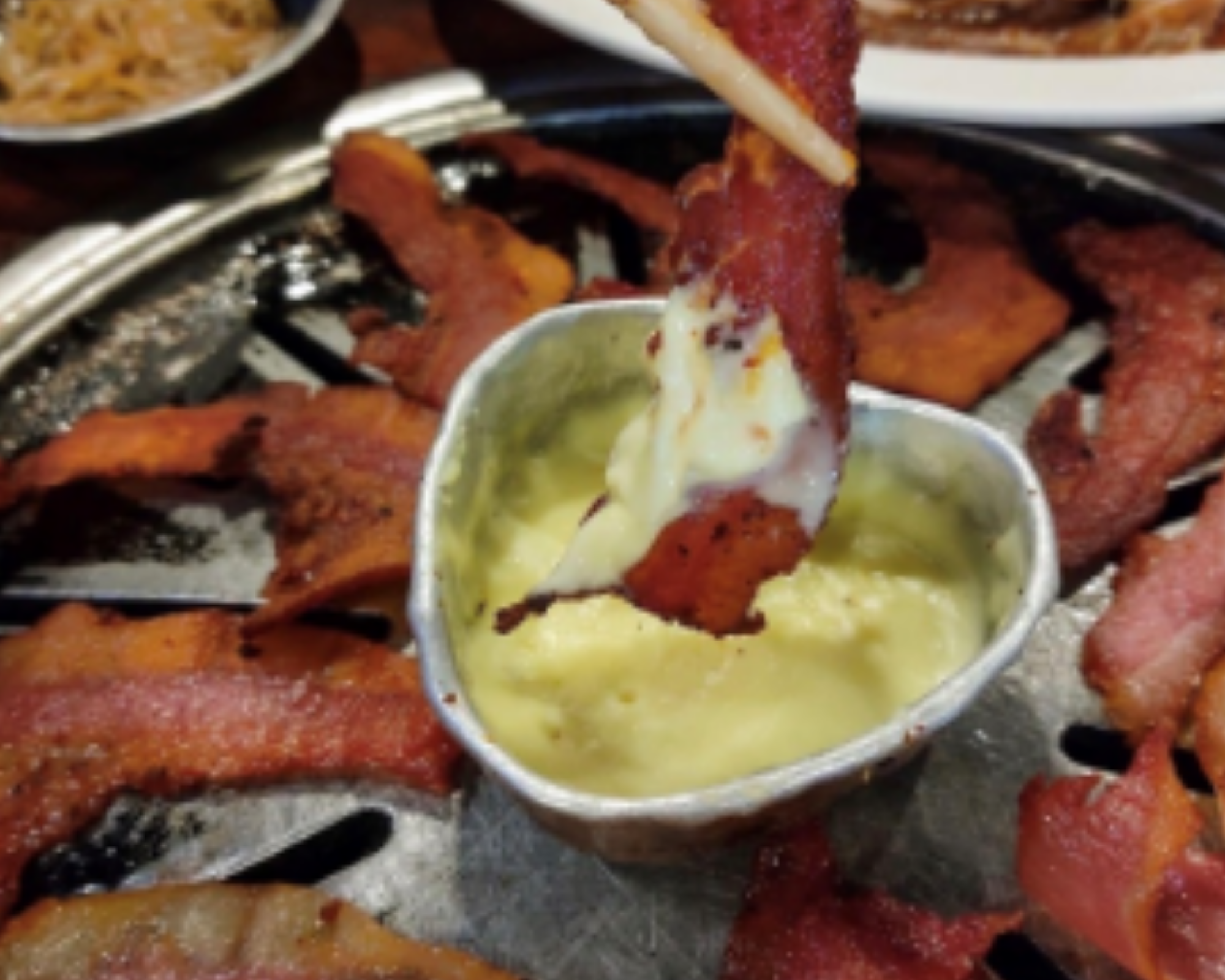 A strip of bacon dipped in cheese sauce surrounded by more strips of bacon.