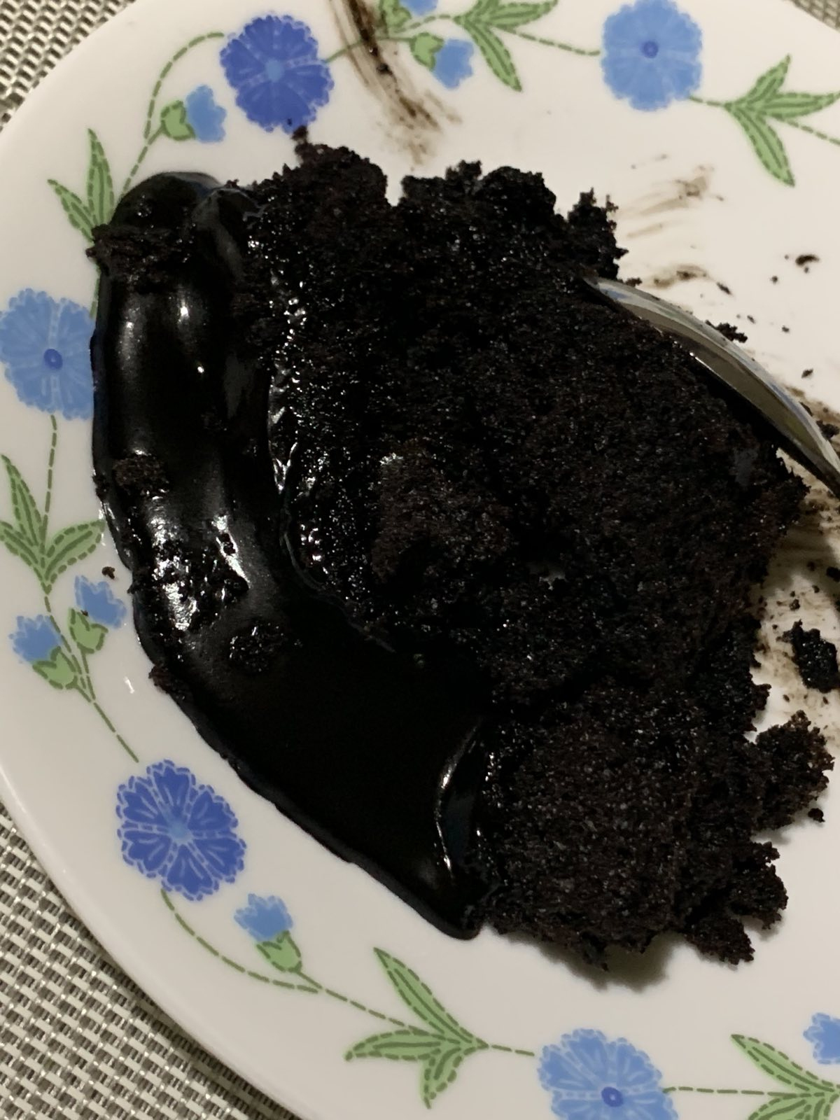 A sticky slice of Big Al's chocolate cake on a saucer.
