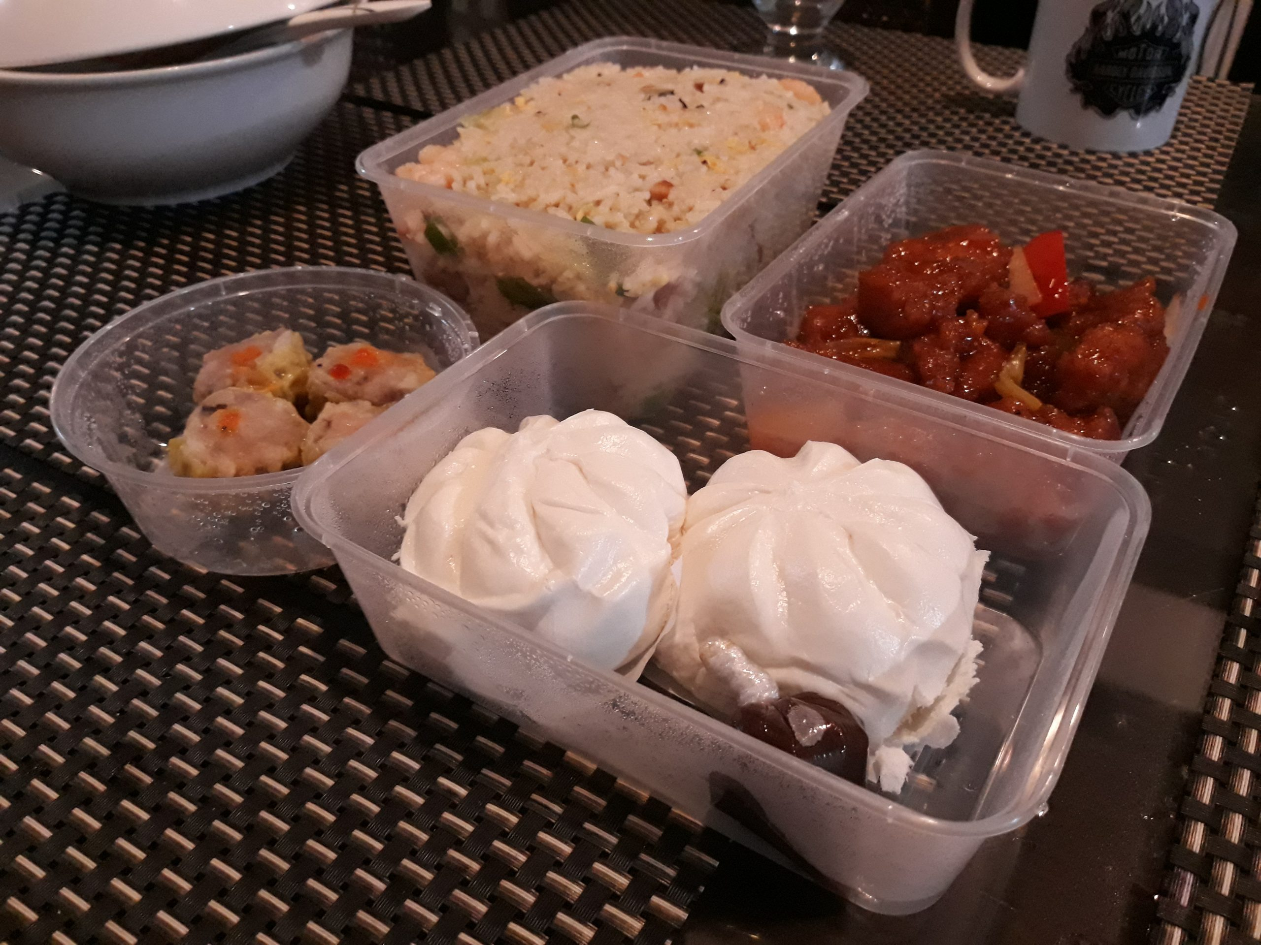 Yang chow, sweet & sour pork, siopao, and siomai in plastic containers.