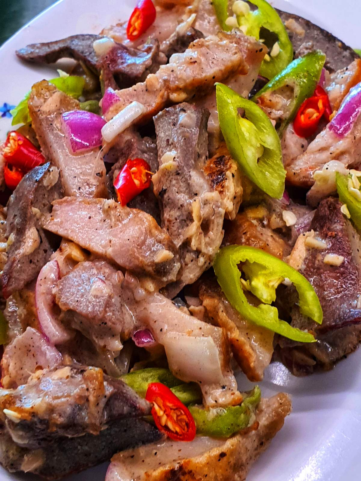 Pieces of pork meat mixed with read and green chilies and onions placed on a white serving plate.
