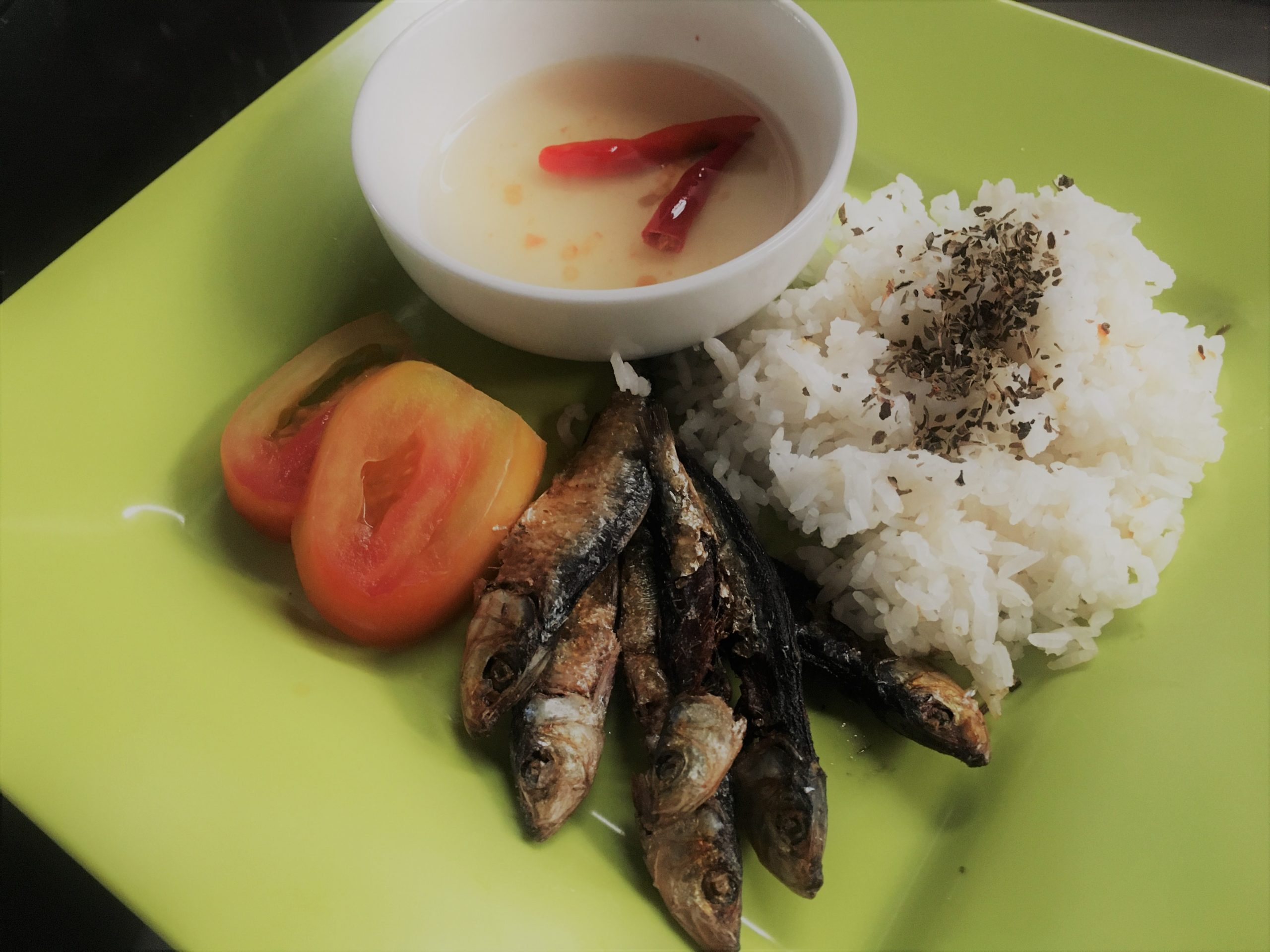 Pieces of dried fish with rice, slices of tomato, and vinegar with chili on a green plate.