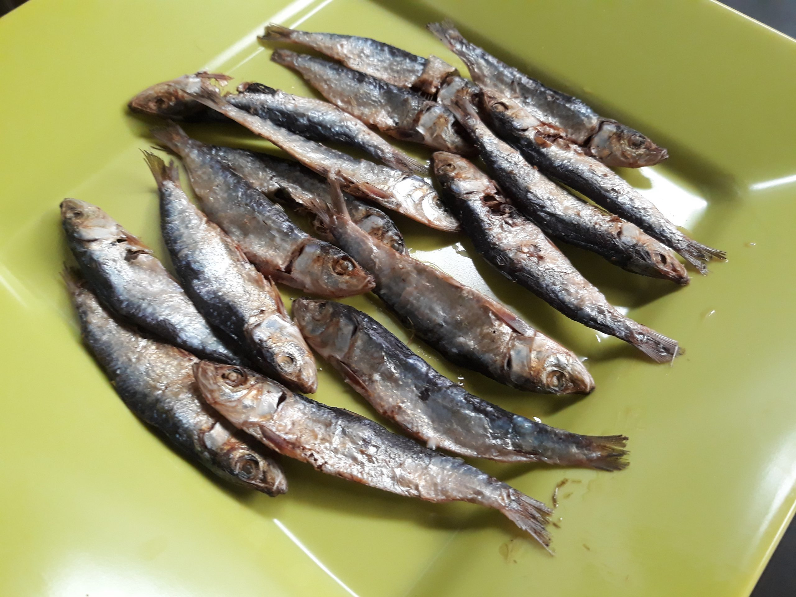 Pieces of dried fish arranged neatly on a green plate.