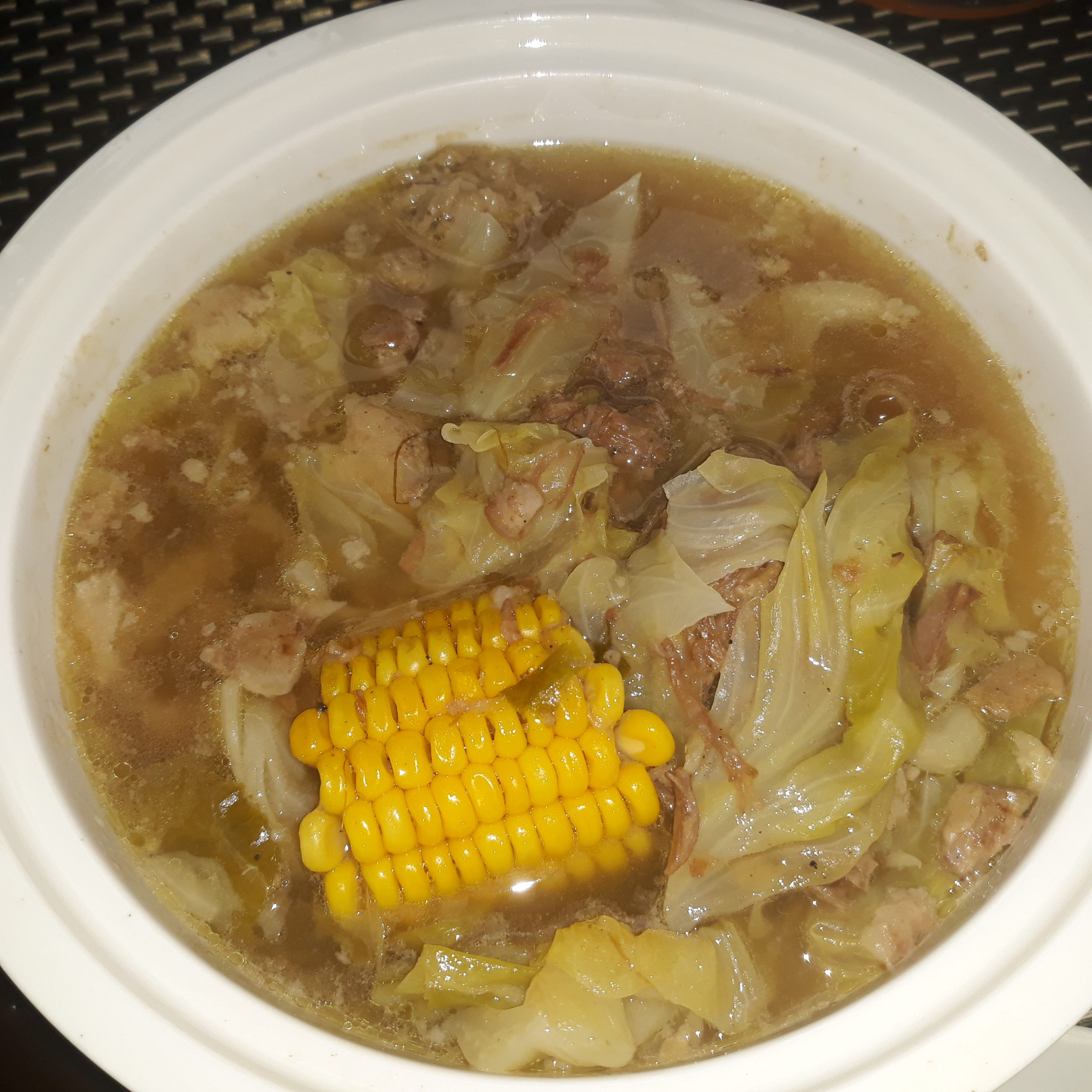 Left-over bulalo showing a piece of corn and shredded cabbage and meat in a white serving bowl.