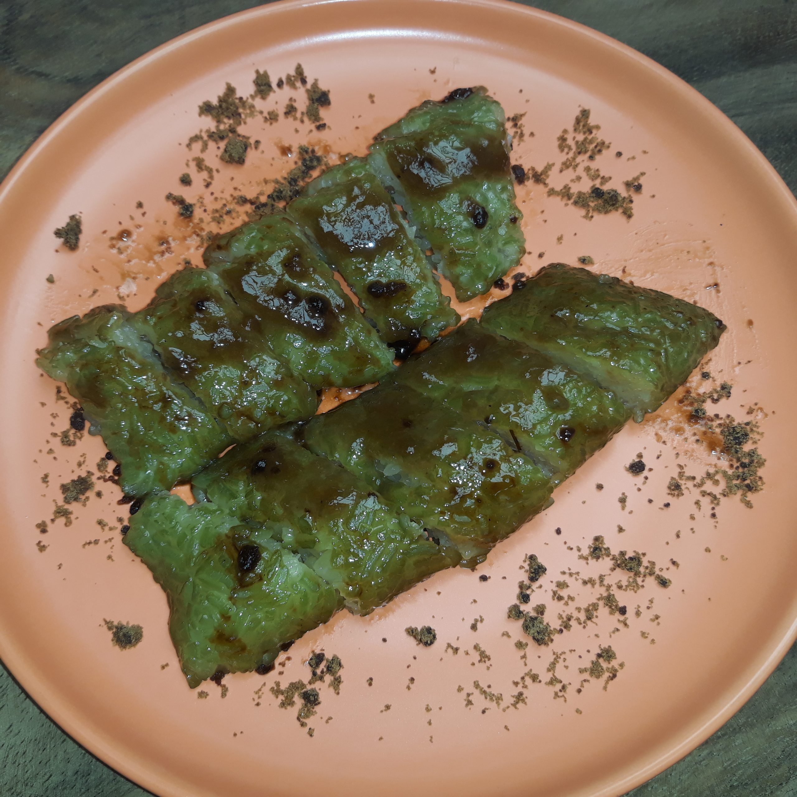 Two pieces of suman sliced into smaller pieces topped with latik.