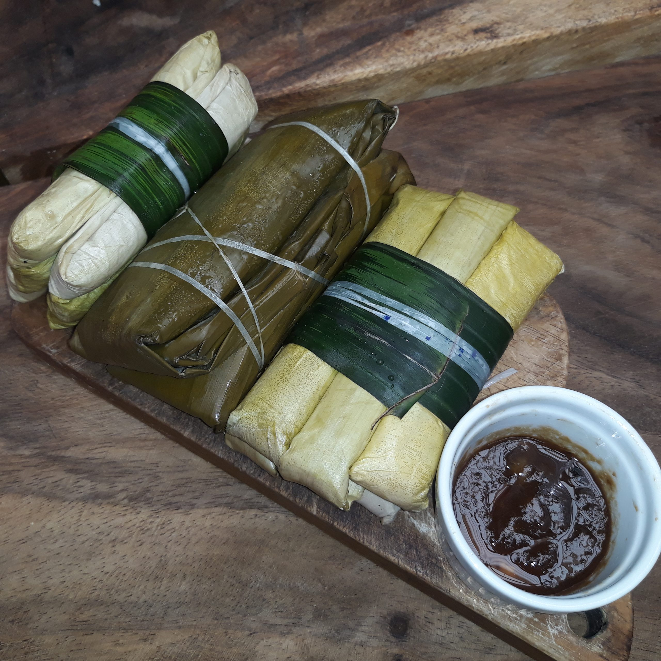 Suman wrapped in banana leaves with latik on the side.