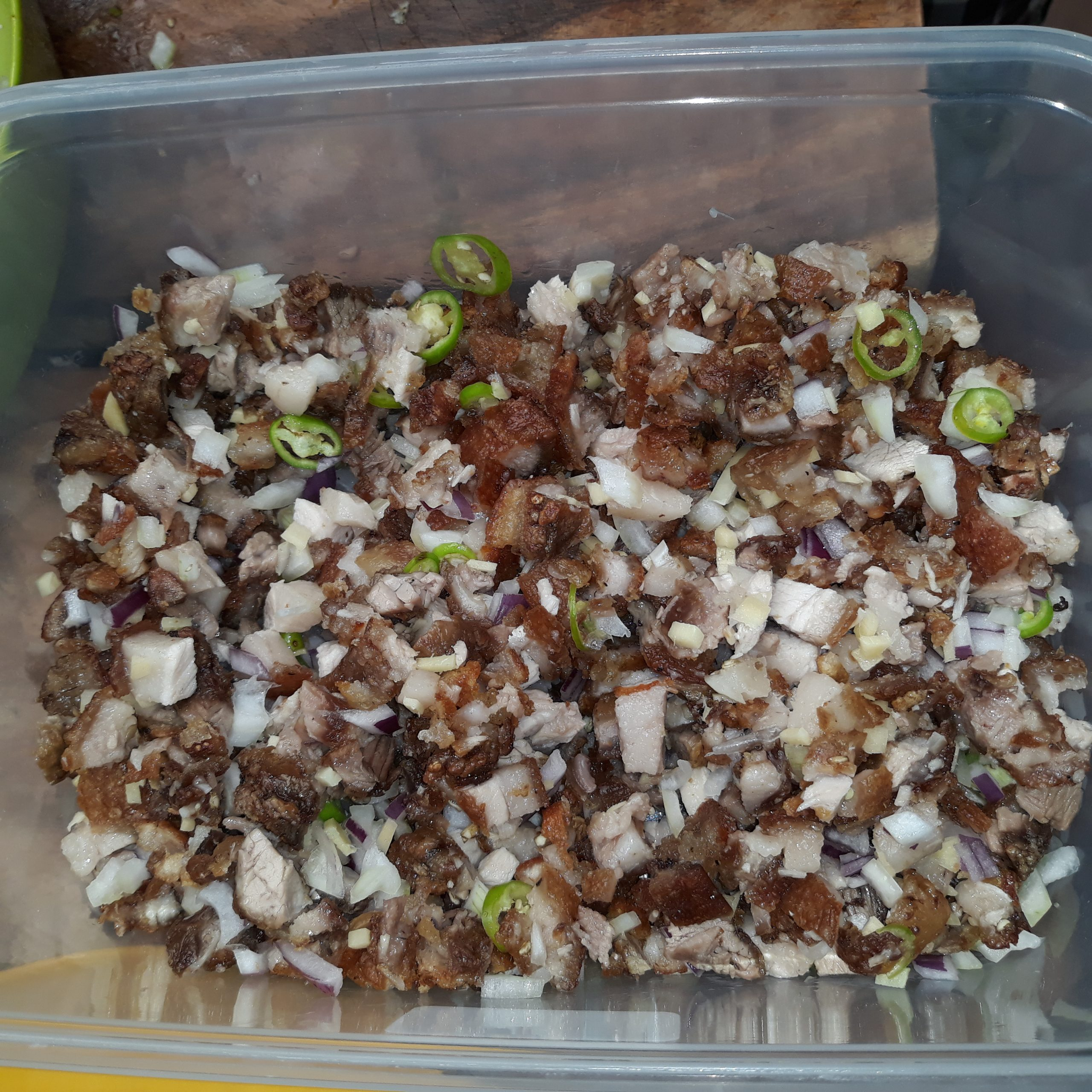 Cooked sisig in a plastic container.