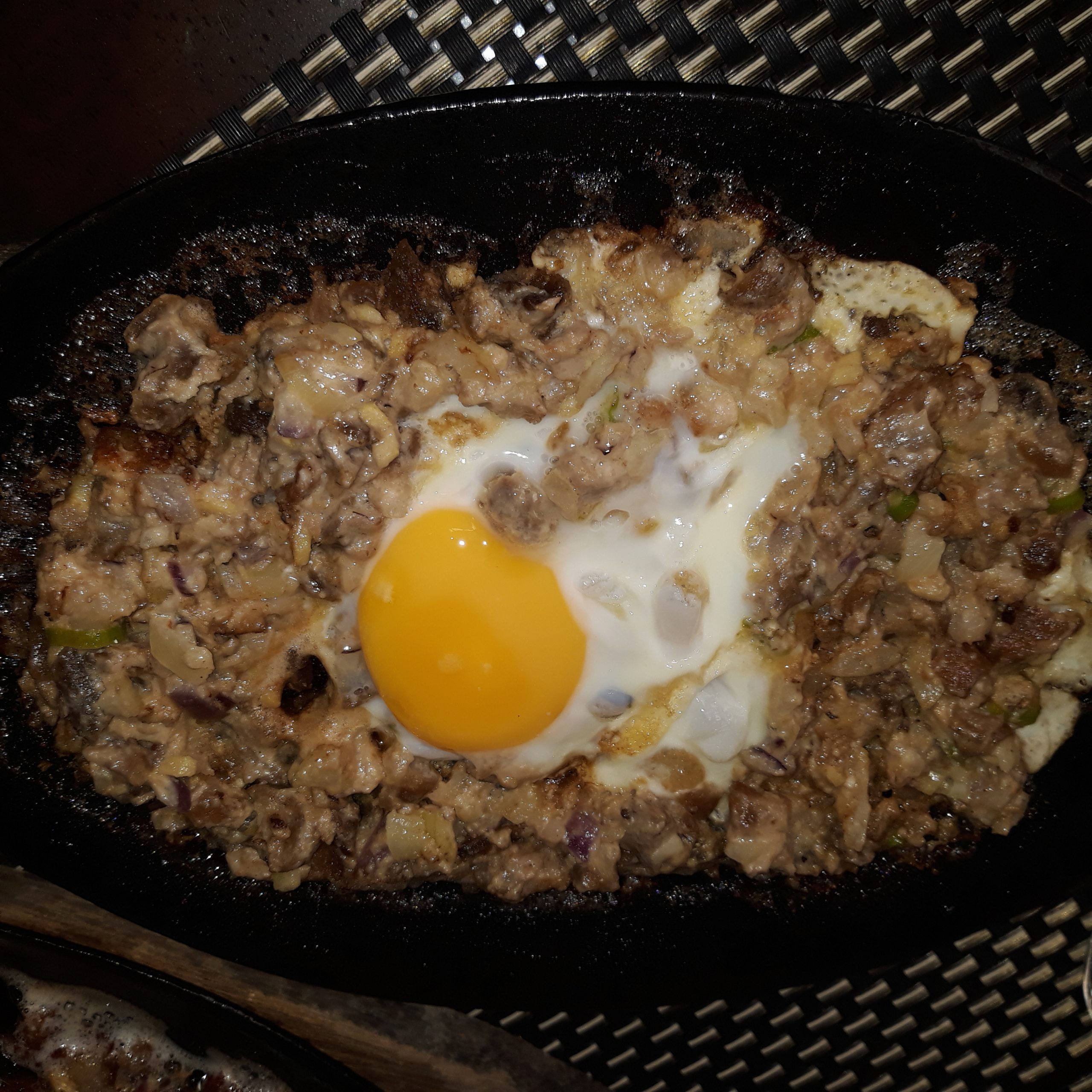 Sisig on a sizzling plate with an egg on top.