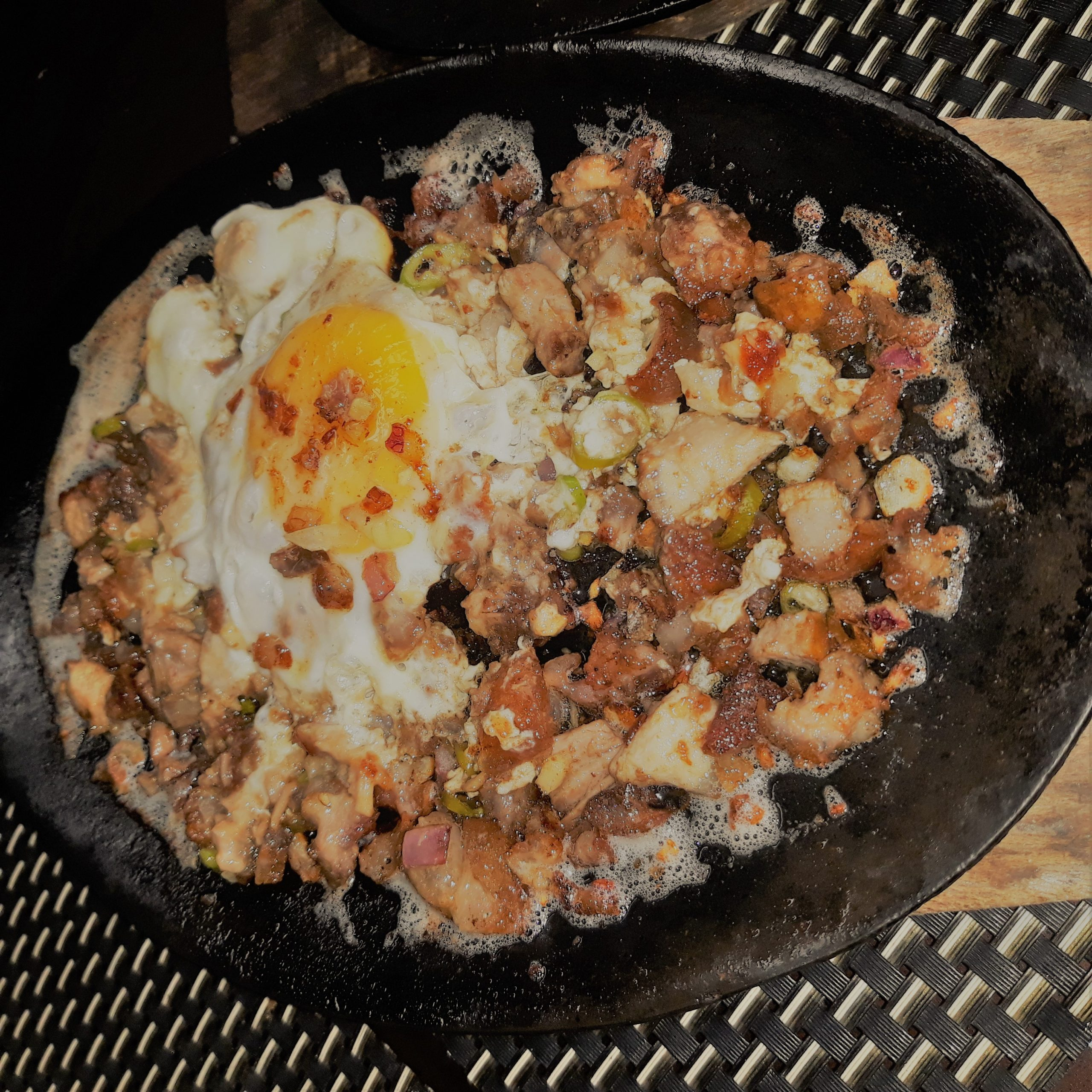 Sizzling sisig with an egg on top.