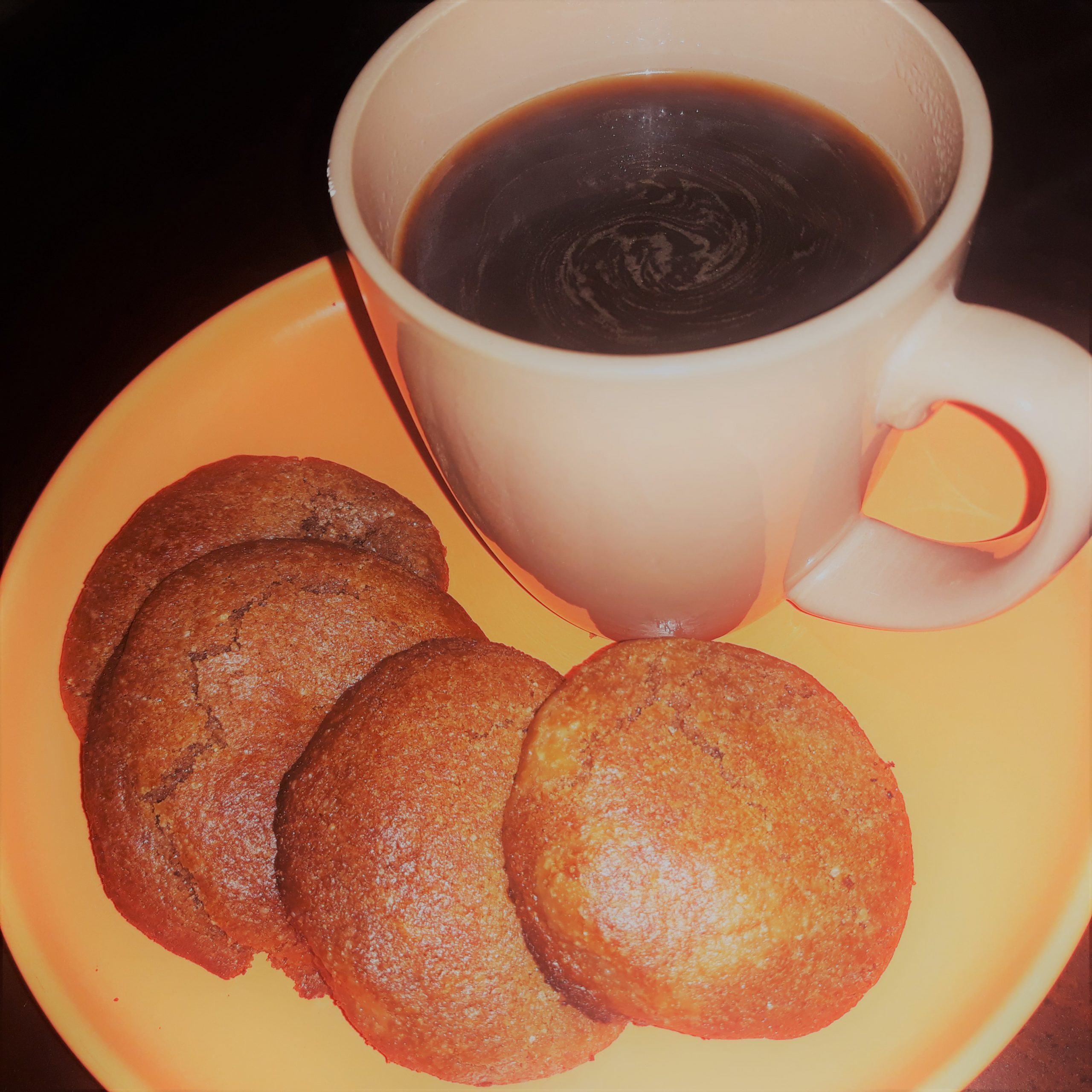 Four pieces of cookies on an orange plate with a brown cup of coffee on the side.