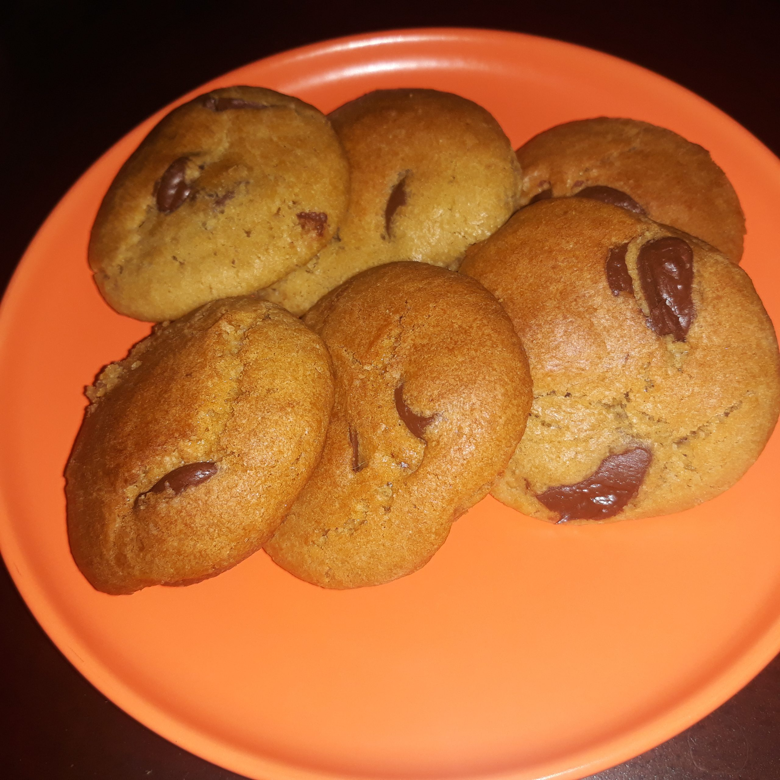 Six pieces of chocolate chip cookies on an orange plate.
