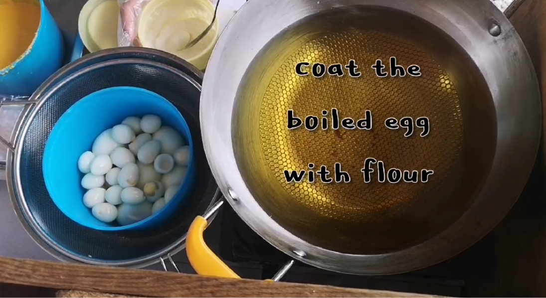Cooking pan filled with oil and quail eggs inside a blue container on the side./
