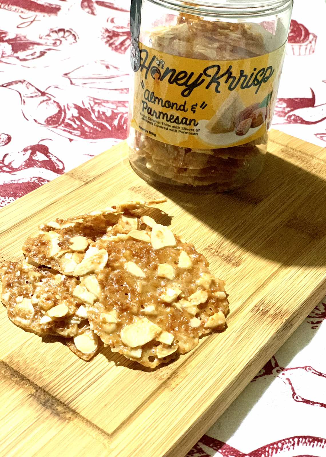 Pieces of Honey Krrisp on a wooden board with a bottle on the side.