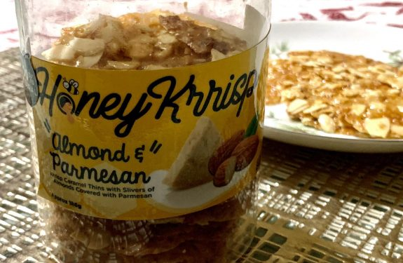 A bottle of Honey Krisp with a plate behind it.