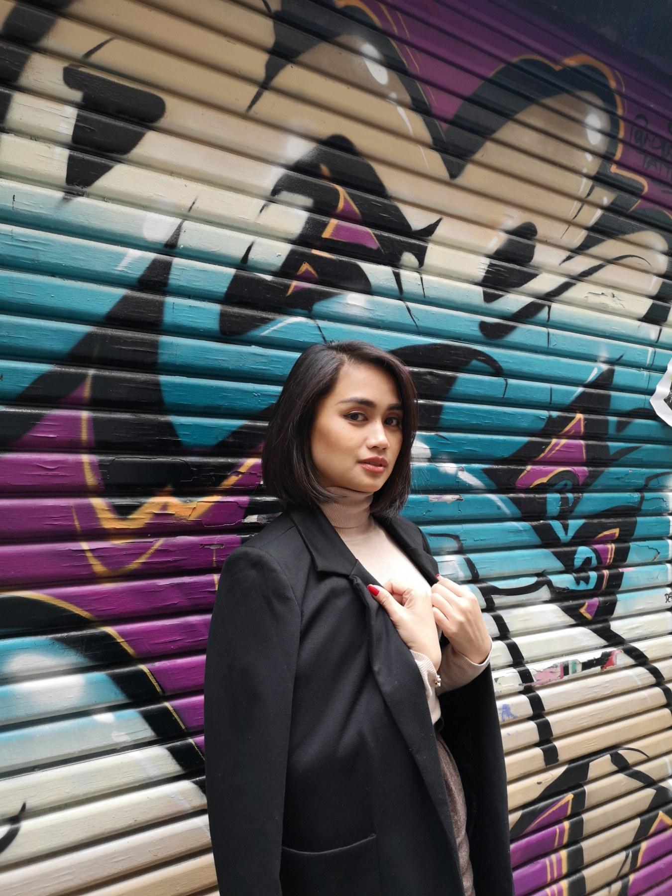 Leigh Nazaredo wearing a blazer and posing against a graffiti wall.