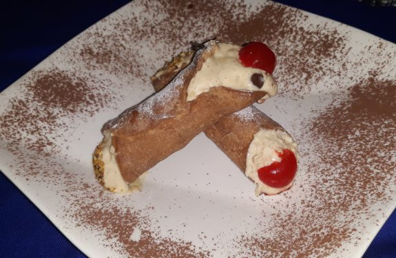 two pieces of cannoli on a white plate