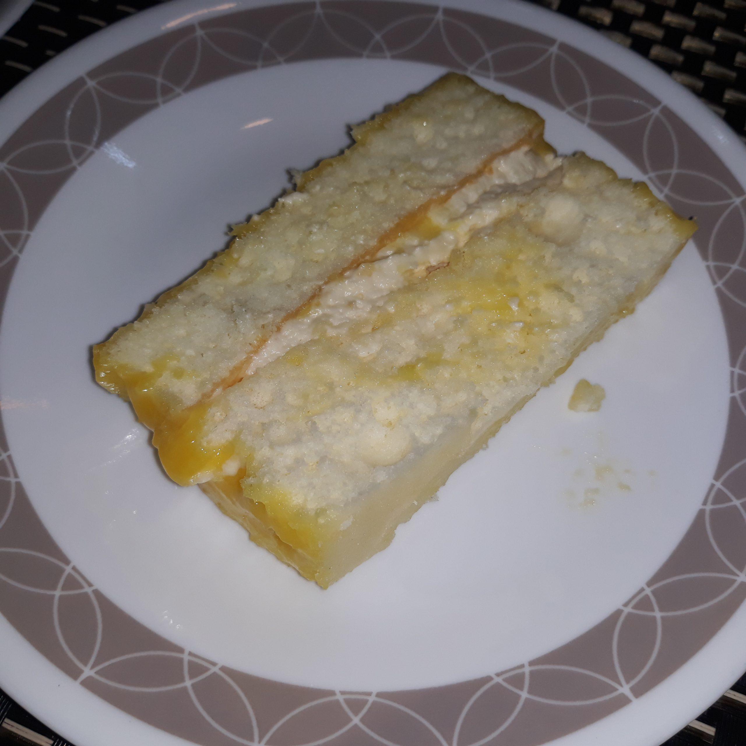 A slice of yema cake on a white plate.