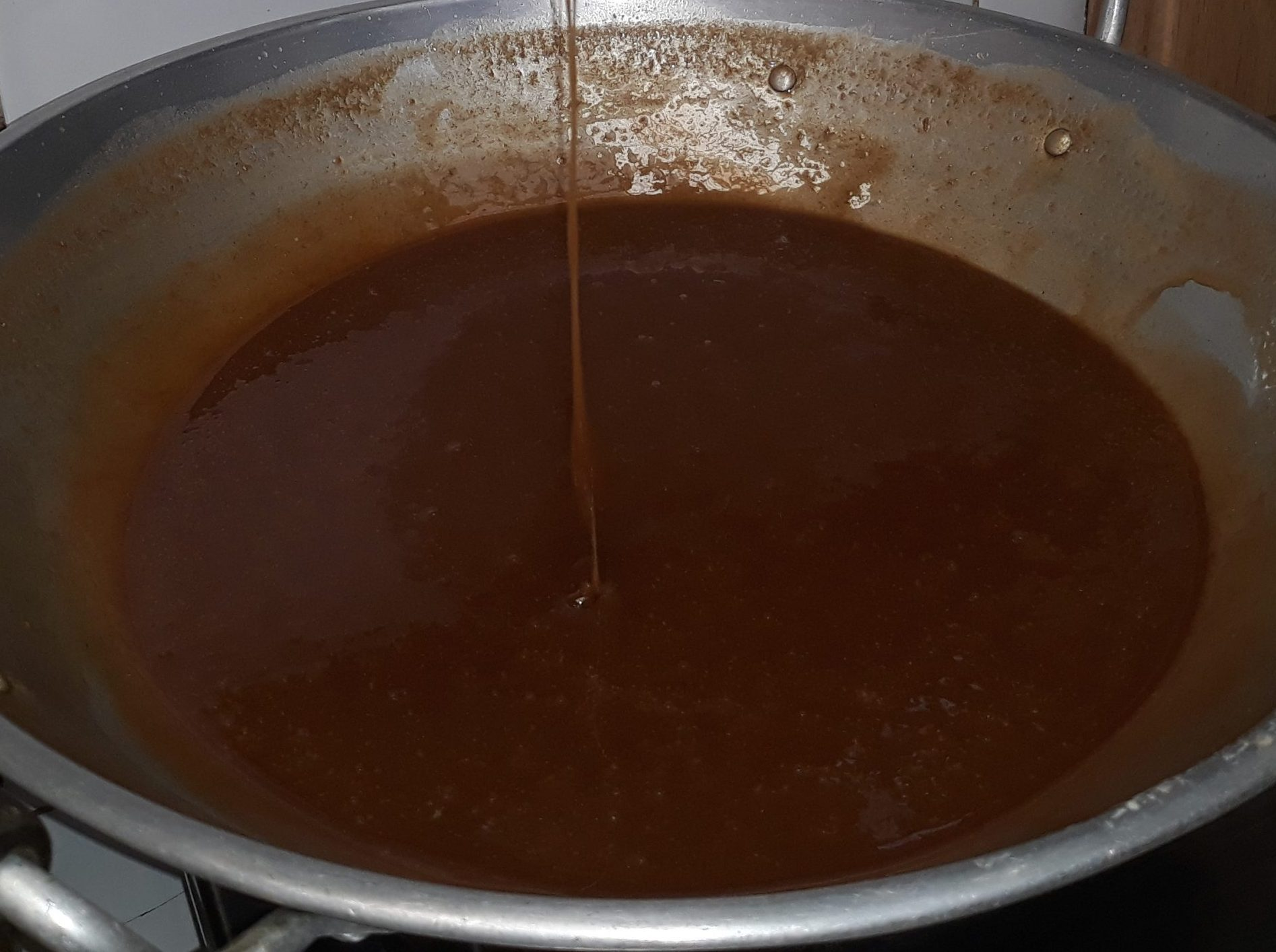 Mixing the freshly squeezed coconut milk and brown sugar until it thickens.