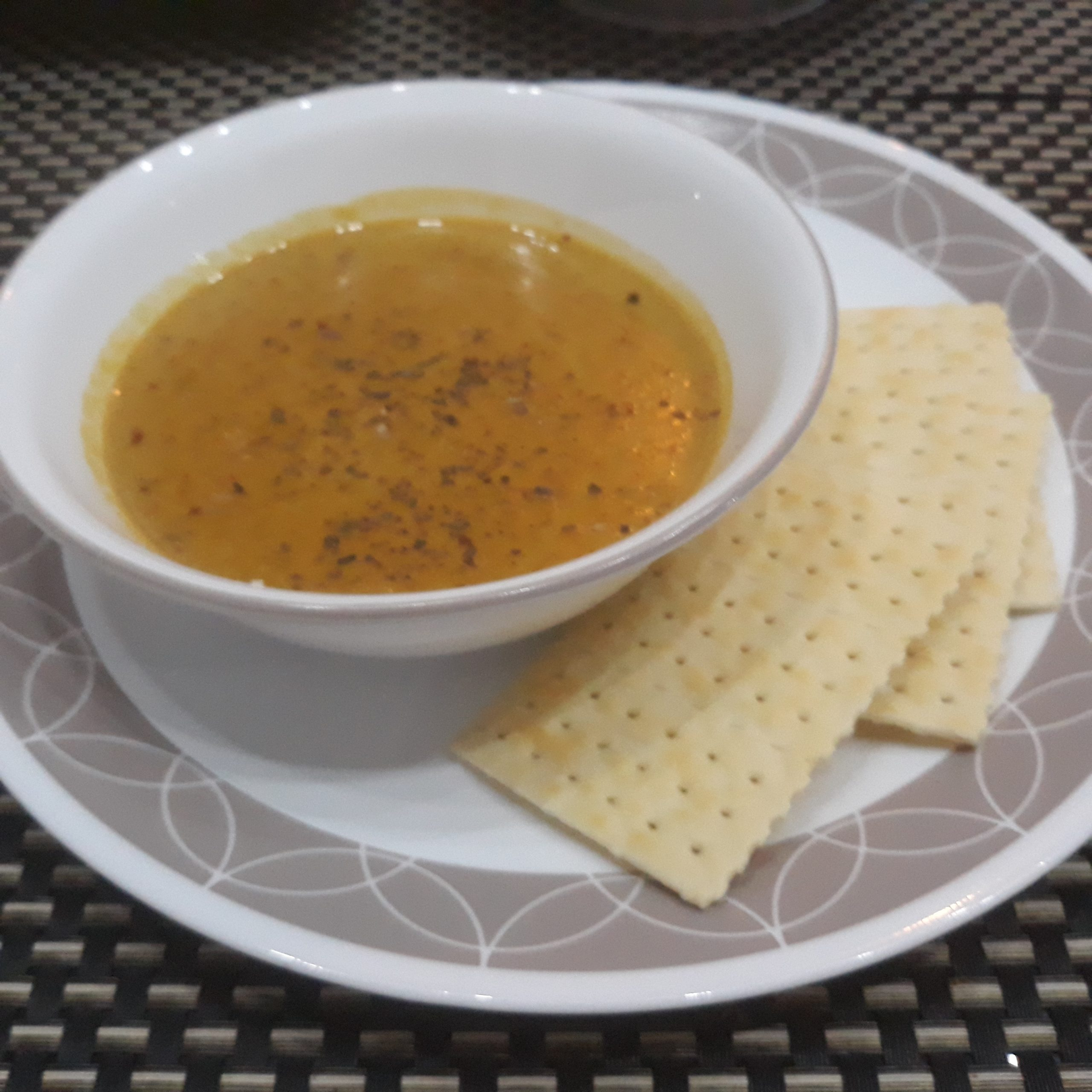 A bowl of kalabasa soup with some Sky Flakes crackers on the side.