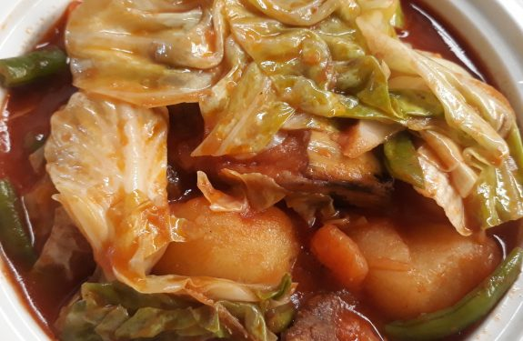 A pochero dish showing some cabbage, string beans, potatoes, and beef in a serving bowl.