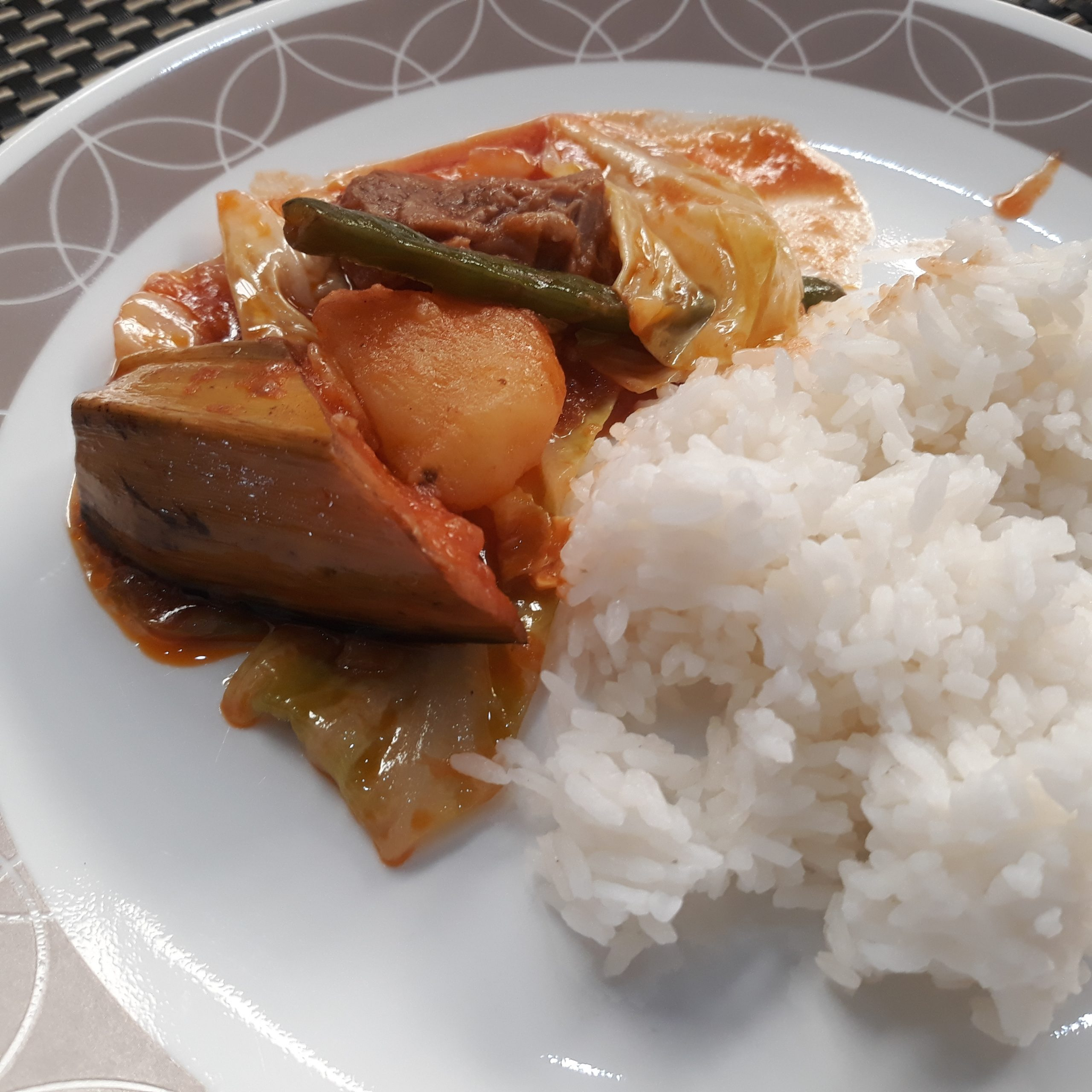 Pochero with rice showing half of a saging na saba with peel.