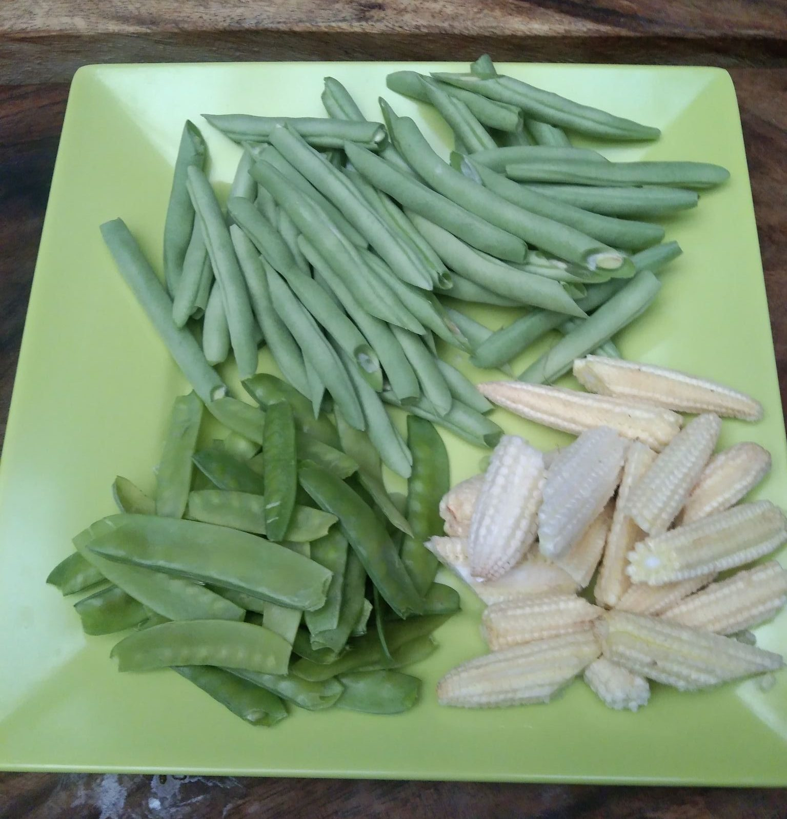Pieces of baby corn, snow peas, and string beans on a green plate.