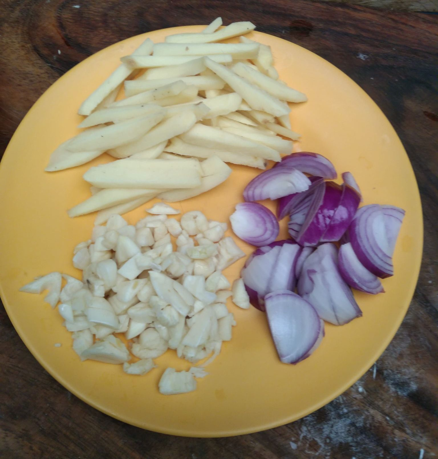 Chopped onions, garlic, and ginger on a yellow plate.