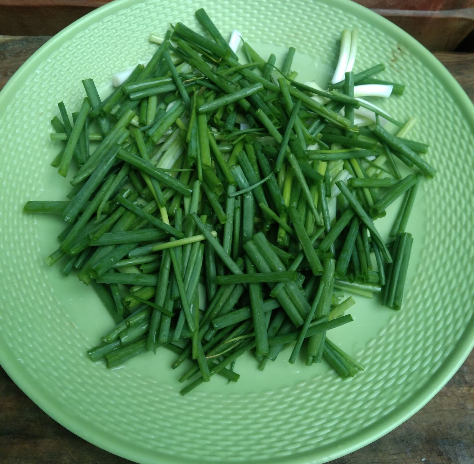 Chopped onion leaves on a green plate.