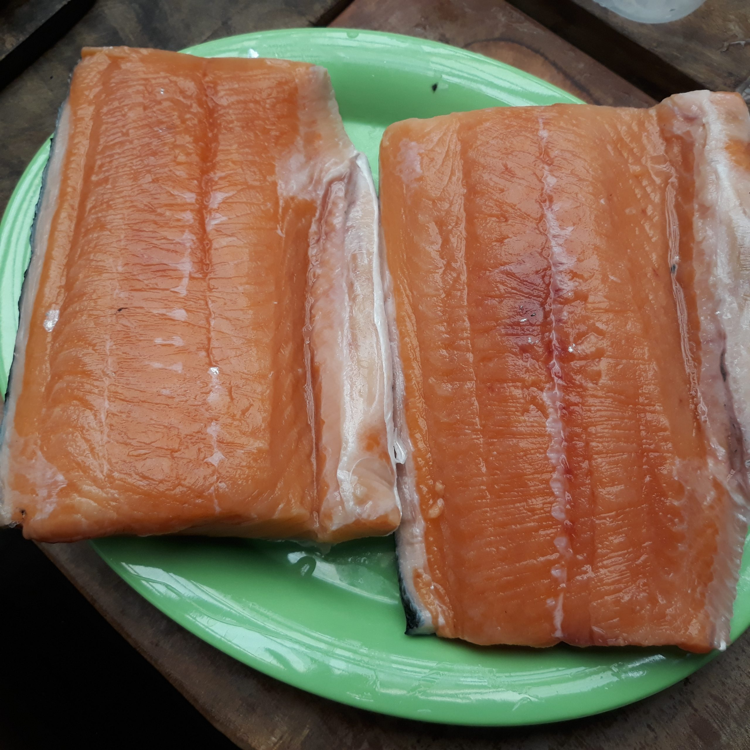 Two pieces of salmon fillet on a green plate.