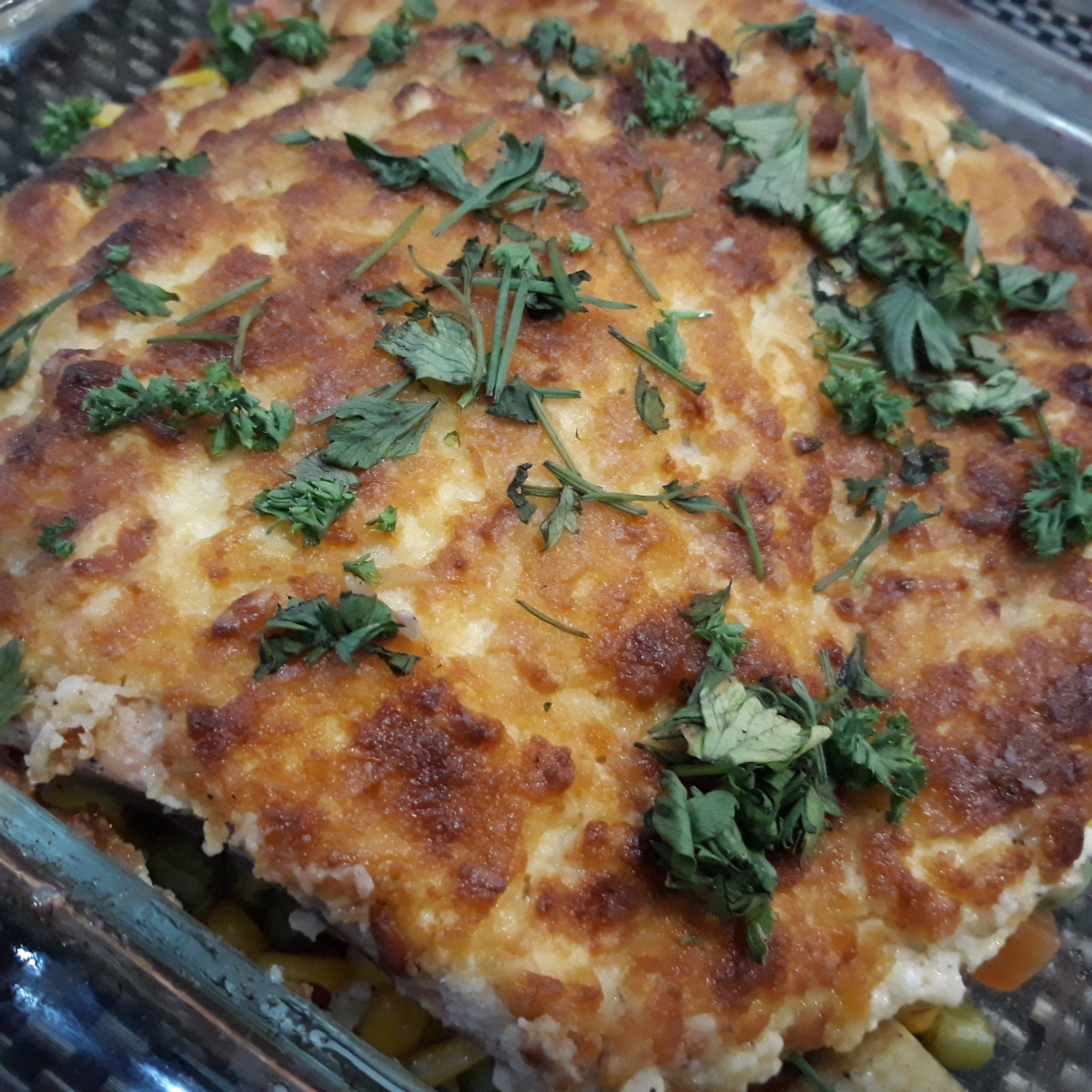 Baked salmon ala Contis topped with parsley.