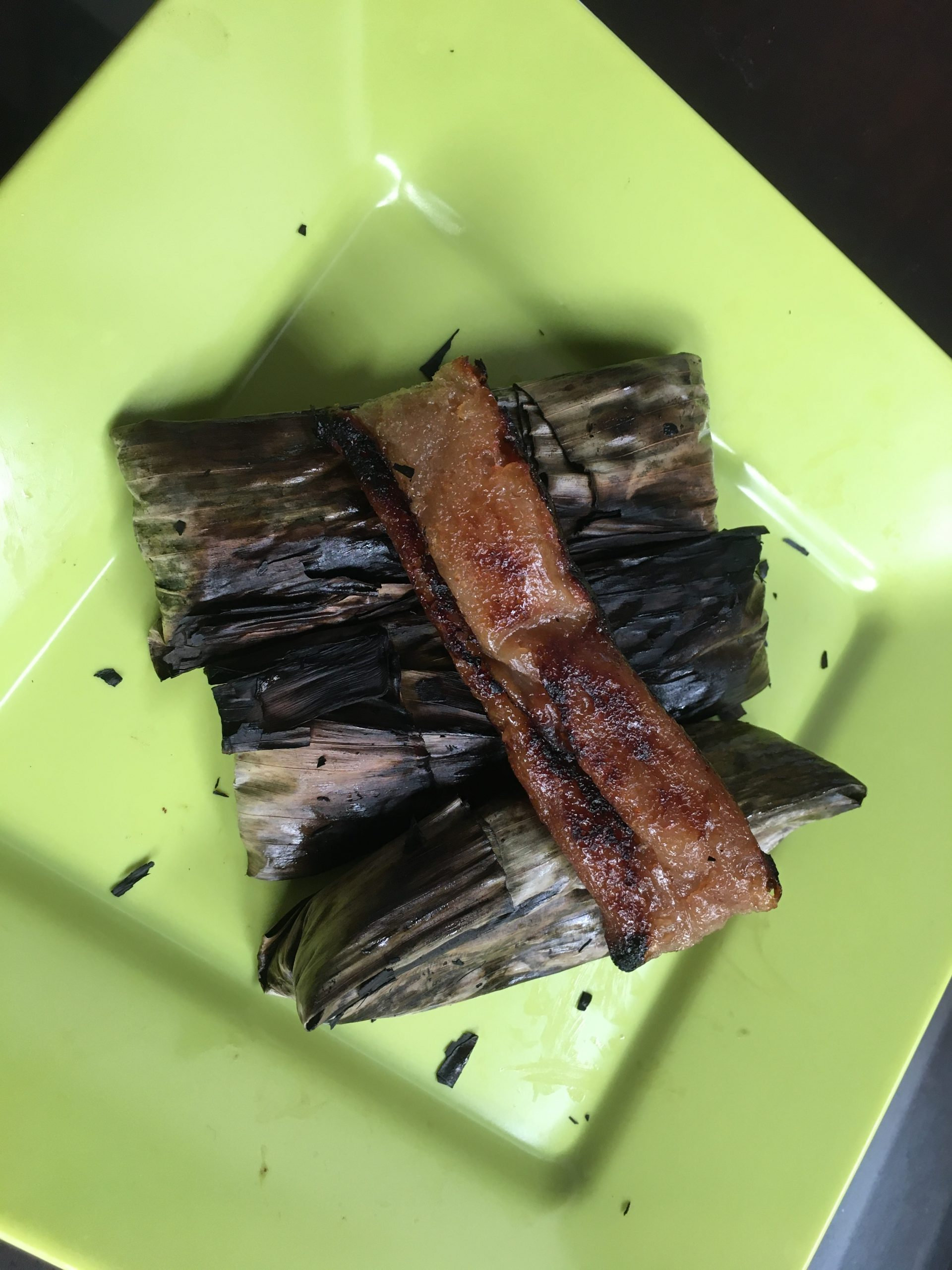 Wrapped tupig with on a green plate topped with an unwrapped tupig.