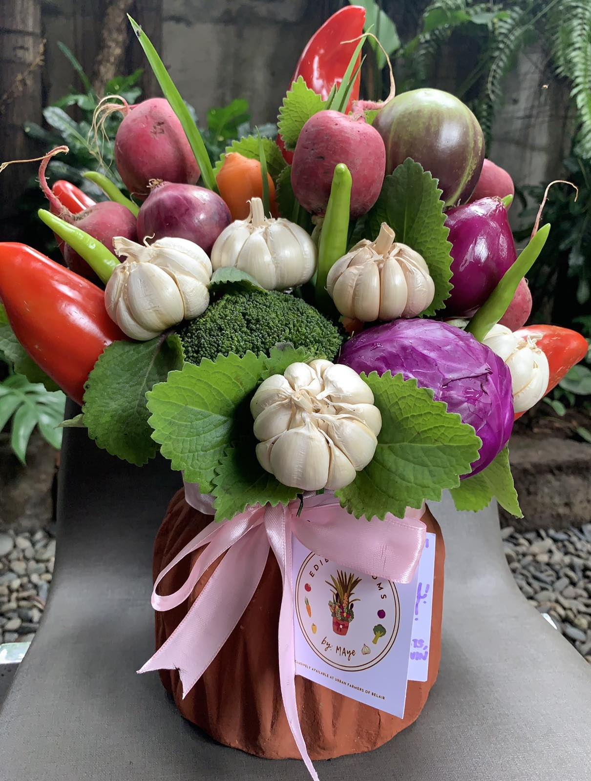 Garlic, bell pepper, onions, radish, broccoli, and chilies beautifully arranged in a terracotta pot.