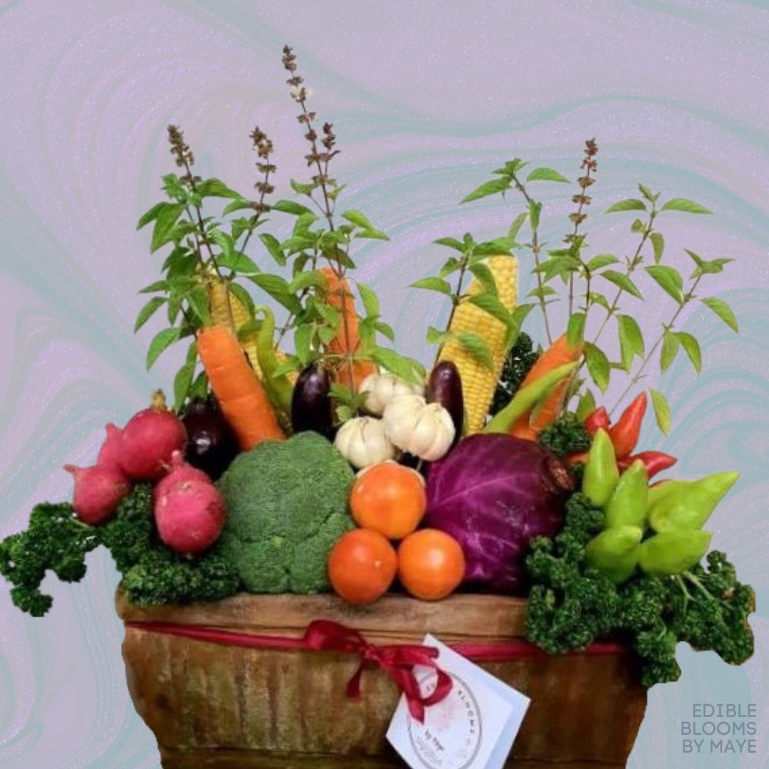 Broccoli, tomatoes, red chilis, green chilis, eggplant, corn, carrots neatly arranged in a terra-cotta pot.
