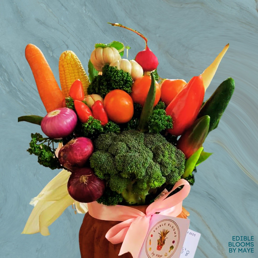 Carrots, corn, onions, garlic, broccoli, chilis, and cucumber replace flowers in colorful arrangement.