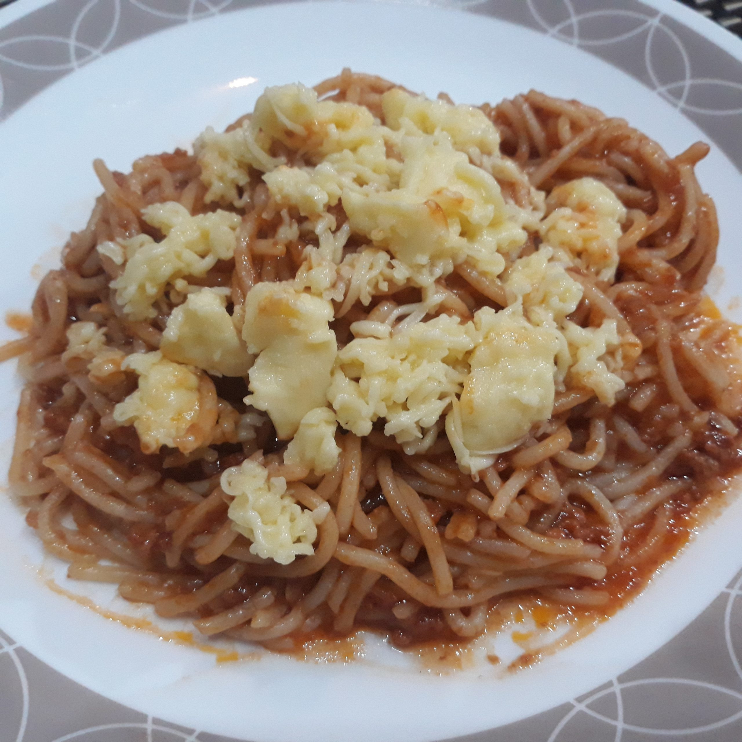 Filipino-style spaghetti topped with lots of cheese.