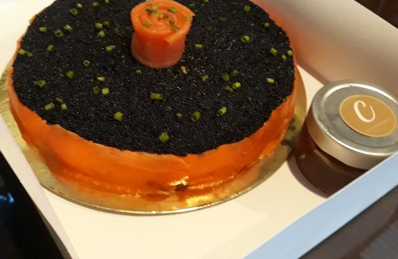 Caviar cake in a box with a small bottle of honey on the side.